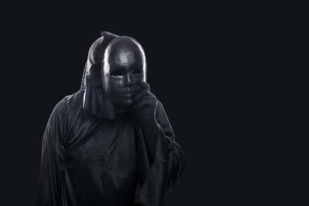 Scary figure in hooded cloak with mask in hand isolated on black background Фото со стока