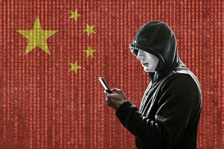 Hacker chino encapuchado con máscara con smartphone Foto de archivo