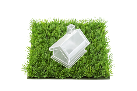 Crystal house on green grass field isolated on white background