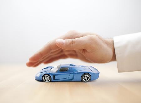Concetto di assicurazione auto con giocattolo auto blu coperto a mano