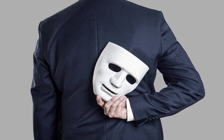Business fraud concept. Businessman hide the mask in his hand behind his back. Stockfoto