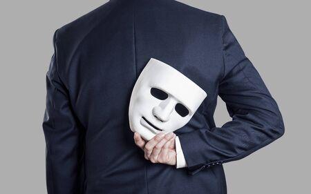 Concetto di frode aziendale. L'uomo d'affari nasconde la maschera in mano dietro la schiena.