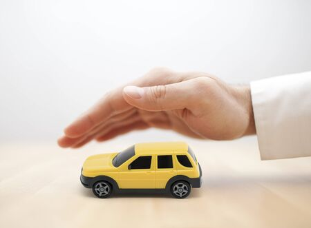 Car insurance concept with yellow car toy covered by hand