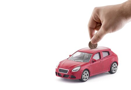 Putting coin into the car on a bank. On white background Stock fotó