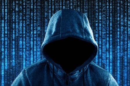 Anonymous hooded computer hacker portrait on computer code background