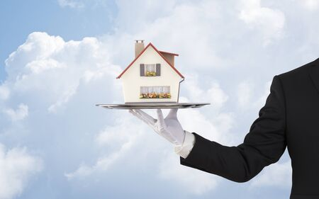 Businessman offering house model on silver tray