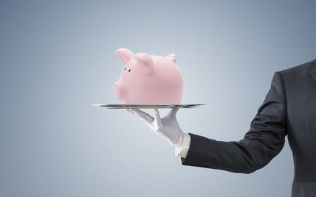 Businessman offering a pink piggy bank on a silver tray