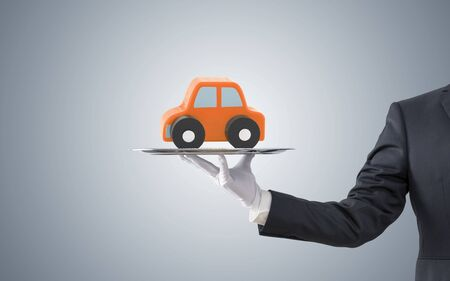 Businessman offering orange car on silver tray Stock Photo