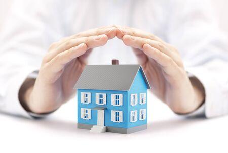 Pequeña casa azul cubierta por manos