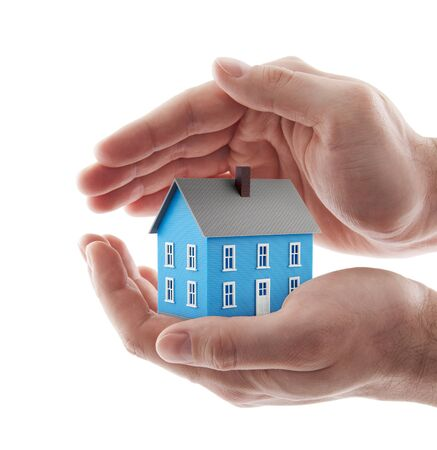 Small blue toy house protected by hands isolated on white