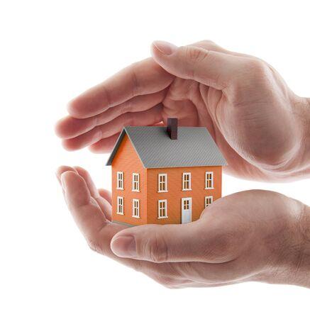 Pequeña casa de juguete naranja protegida por manos aisladas en blanco