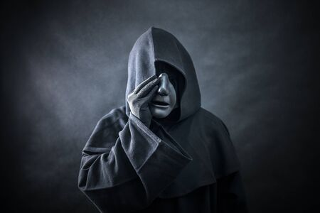 Ghostly figure in hooded cloak. Scary figure with part of mannequin head in hands Stock Photo