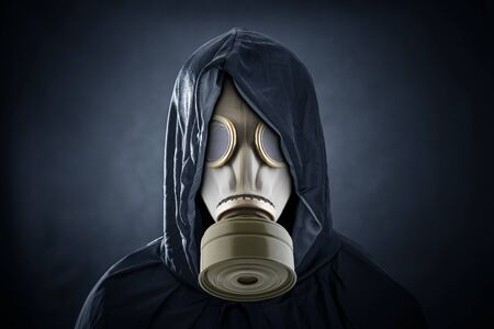 Man in a gas mask and hooded cloak. Environment pollution. Stock Photo