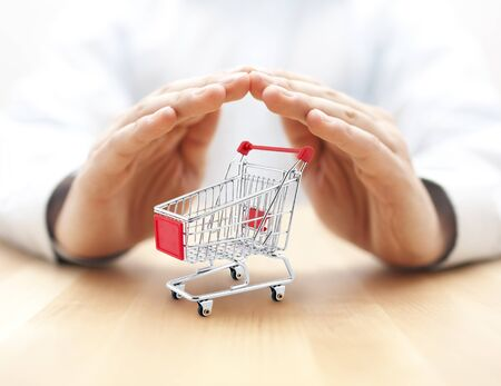 Shopping cart protected by hands. Secure purchase concept. Foto de archivo