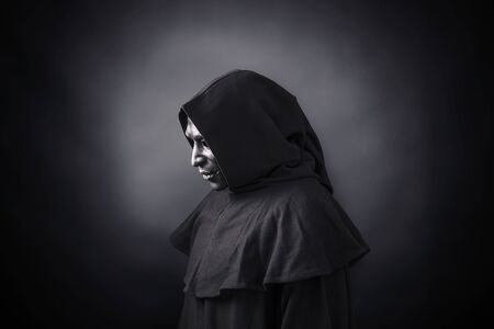 Scary figure in hooded cloak with mask Stockfoto