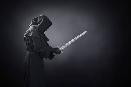 Ghostly figure with medieval sword in the dark