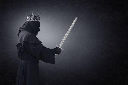 Geist einer Königin oder eines Königs mit mittelalterlichem Schwert im Dunkeln Standard-Bild