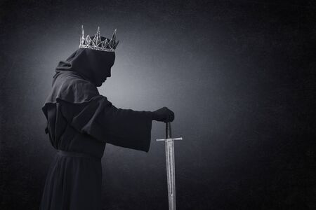 Ghost of a queen or king with medieval sword in the dark Imagens