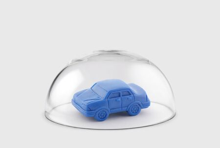 Blue toy car protected under a glass dome
