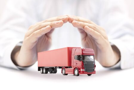 Red long truck with a trailer protected by hands