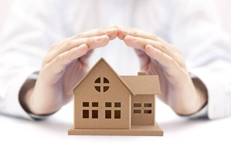 Property insurance. House miniature covered by hands.