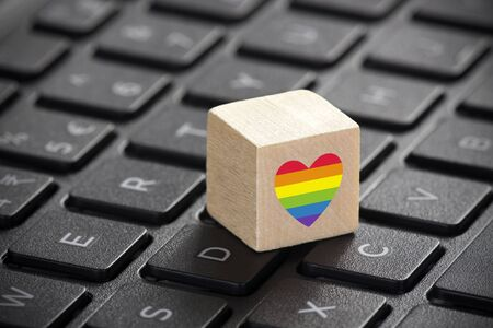 Wooden block with LGBT rainbow heart symbol of love on laptop keyboard.