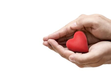 Red heart in hands. Health insurance or love concept Foto de archivo
