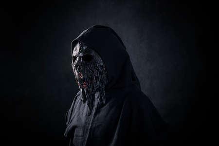 Scary figure in hooded cloak with mask Foto de archivo