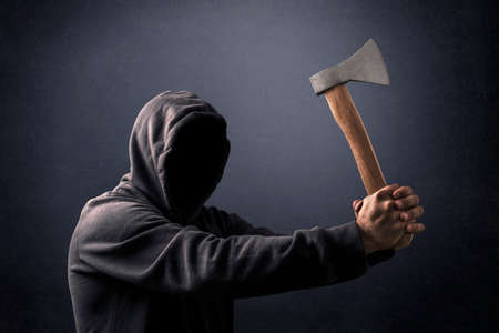 Hooded man with an ax in the dark Banque d'images
