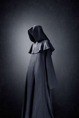 Scary figure in hooded cloak Фото со стока
