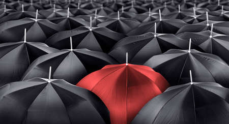 Different, unique and standing out of the crowd red umbrella. Leader or being different concept Banco de Imagens