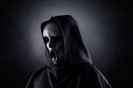 Ghostly figure in hooded cloak in the dark