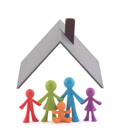 Colorful family figurines covered by house roof on white background 免版税图像