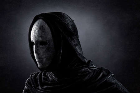 Scary figure with hooded cape in the dark
