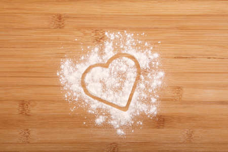 Heart made of flour on a wooden bamboo background