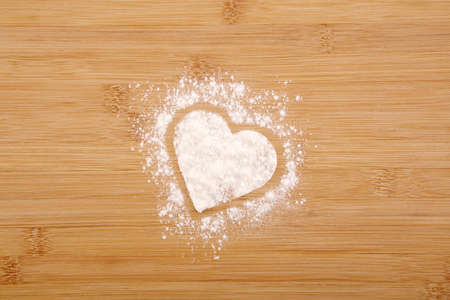 Heart made of flour on a wooden bamboo background Stock Photo