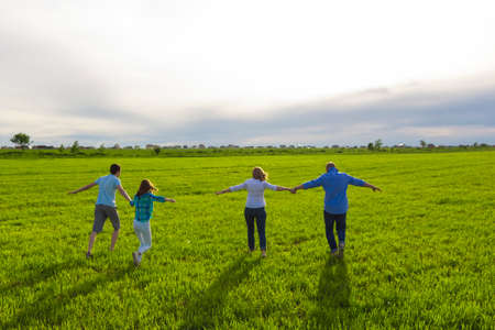 Family runs on the green lawn. Adult children. Holiday, summer.