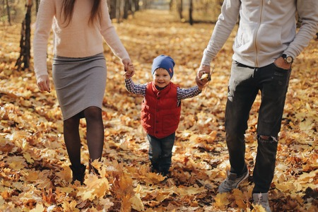 Family walking with son through autumn forest. Фото со стока