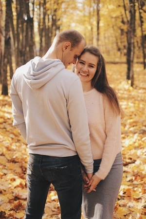 Couple stands in the forest together. Attractive girl hugging her boyfriend and looking at the camera. Happy family stay in autumn park.