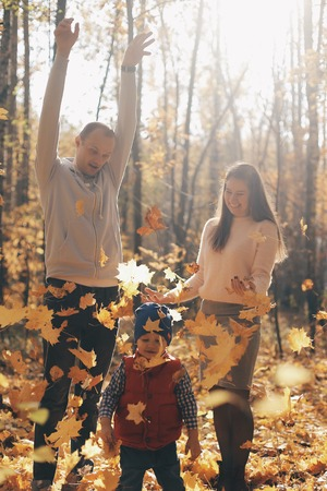 Happy family with son in autumn park throws yellow leaves.