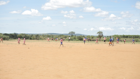 African children and Caucasian people playing football outside together.