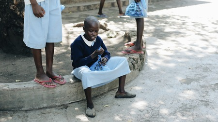 KENYA, KISUMU - MAY 20, 2017: Bald african girl sitting outside near the school and looking inside the bag, open present.