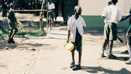 KENYA, KISUMU - MAY 20, 2017: African boy in uniform near school with plastic bottles.