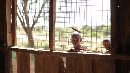 KENYA, KISUMU - MAY 20, 2017: Beautiful African boys peer into a house through the lattice on window.