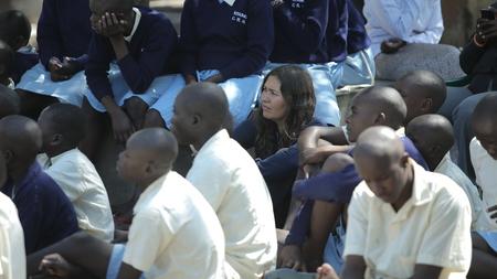 KENYA, KISUMU - MAY 20, 2017: Group of african children and teenagers in uniform sitting on school backyard and looking