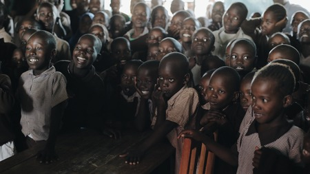 KENYA, KISUMU - MAY 20, 2017: Group of African children in uniform laugh and smile together at lesson at school in Africa.
