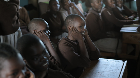 KENYA, KISUMU - MAY 20, 2017: Group of african children in uniform sitting in classroom and looking straight, smiling. Redakční