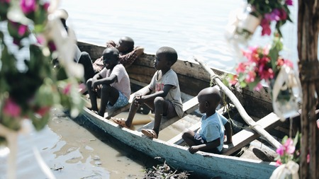 KENYA, KISUMU - MAY 20, 2017: Group of African children sitting in the boat and looking on the water of the sea.