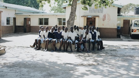 KENYA, KISUMU - MAY 20, 2017: Group of african children sitting on bench. Boys and girls spending time near the school.