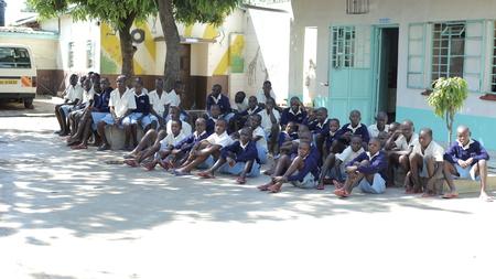 KENYA, KISUMU - MAY 20, 2017: Group of african children sitting on ground. Boys and girls in uniform spend time outside. Redakční